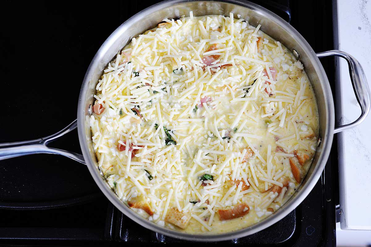 A high sided skillet is on the stove and has a healthy breakfast casserole cooking inside. Chopped prosciutto and shredded mozzarella are on top of the casserole.