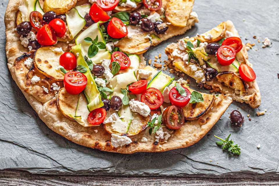 Summer vegetable grilled pizza topped with halved tomatoes, black olives, cheese, zucchini ribbons and sliced potatoes. The pizza is on a slate background and a piece on the right is pulled away from the rest of the pizza.