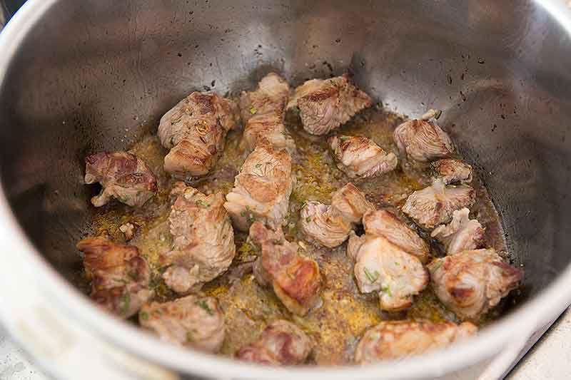 Browned lamb shoulder pieces in pan prepared for lamb stew