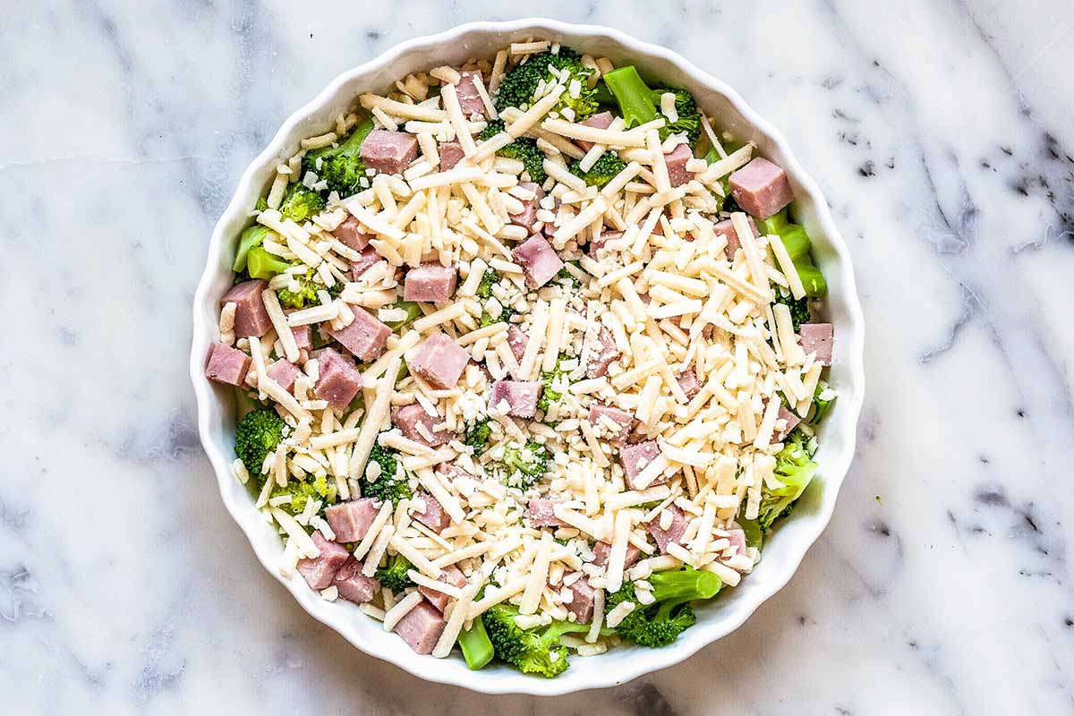Crustless Quiche with Ham - vegetables, cheese, cubed ham in white dish