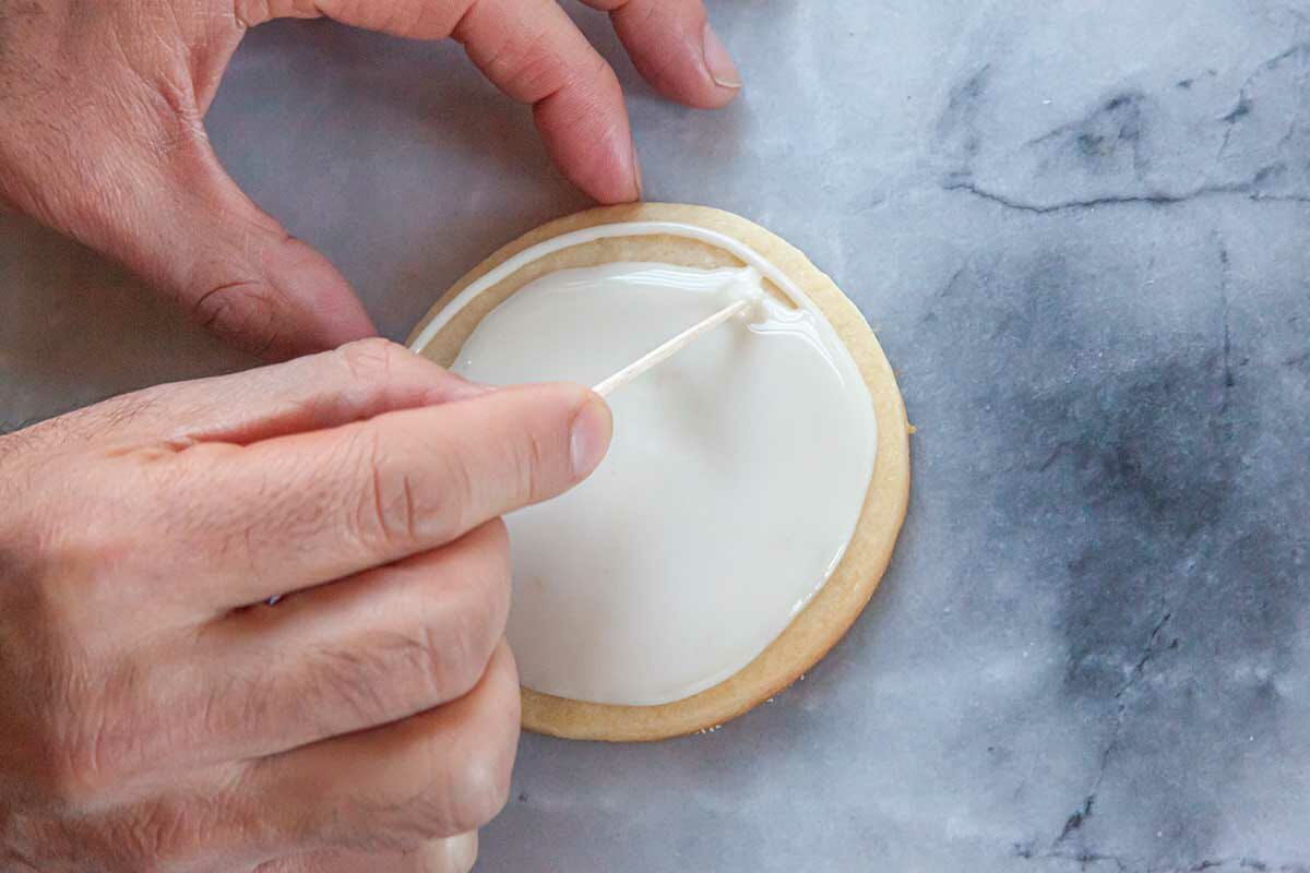 A toothpick used to fill in a sugar cookie with Royal icing.