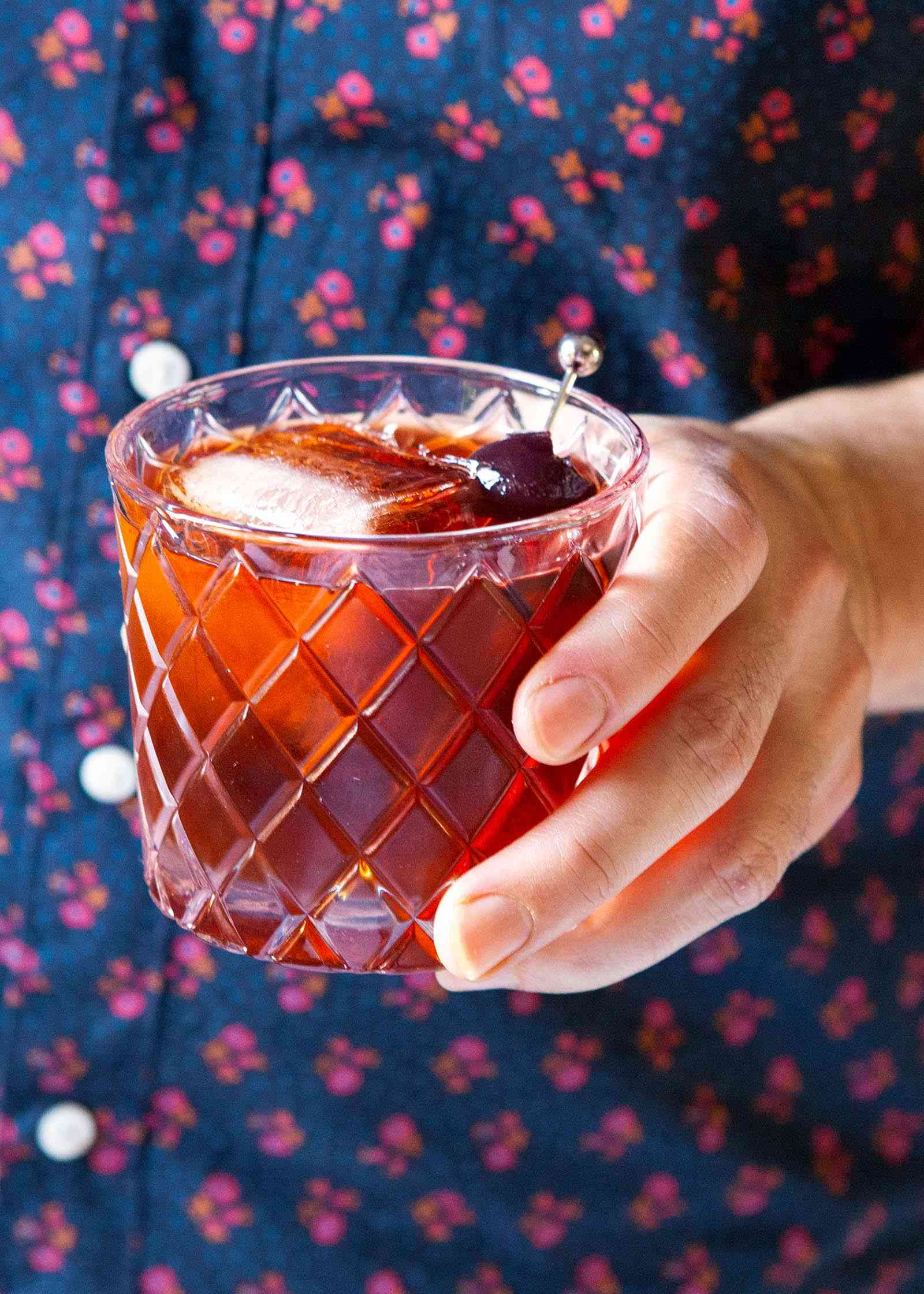 Vieux carre with square ice cubes and a cherry garnish are held in the hand of a person.