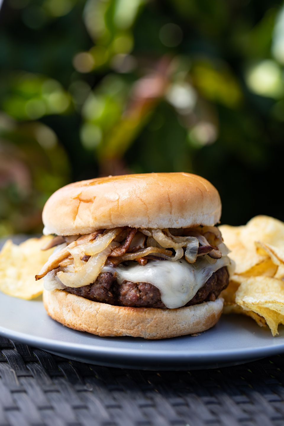 Side view of a mushroom and swiss burger on a plate with chips outside.