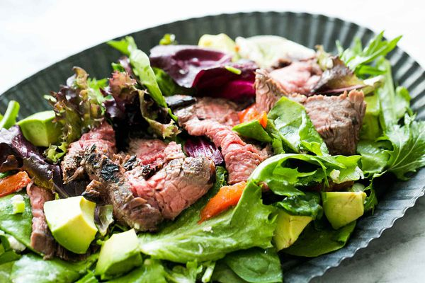 Steak salad made with thinly-sliced pan-seared flank steak on a bed of arugula and lettuce with avocado, pomegranate seeds, and other add-ins