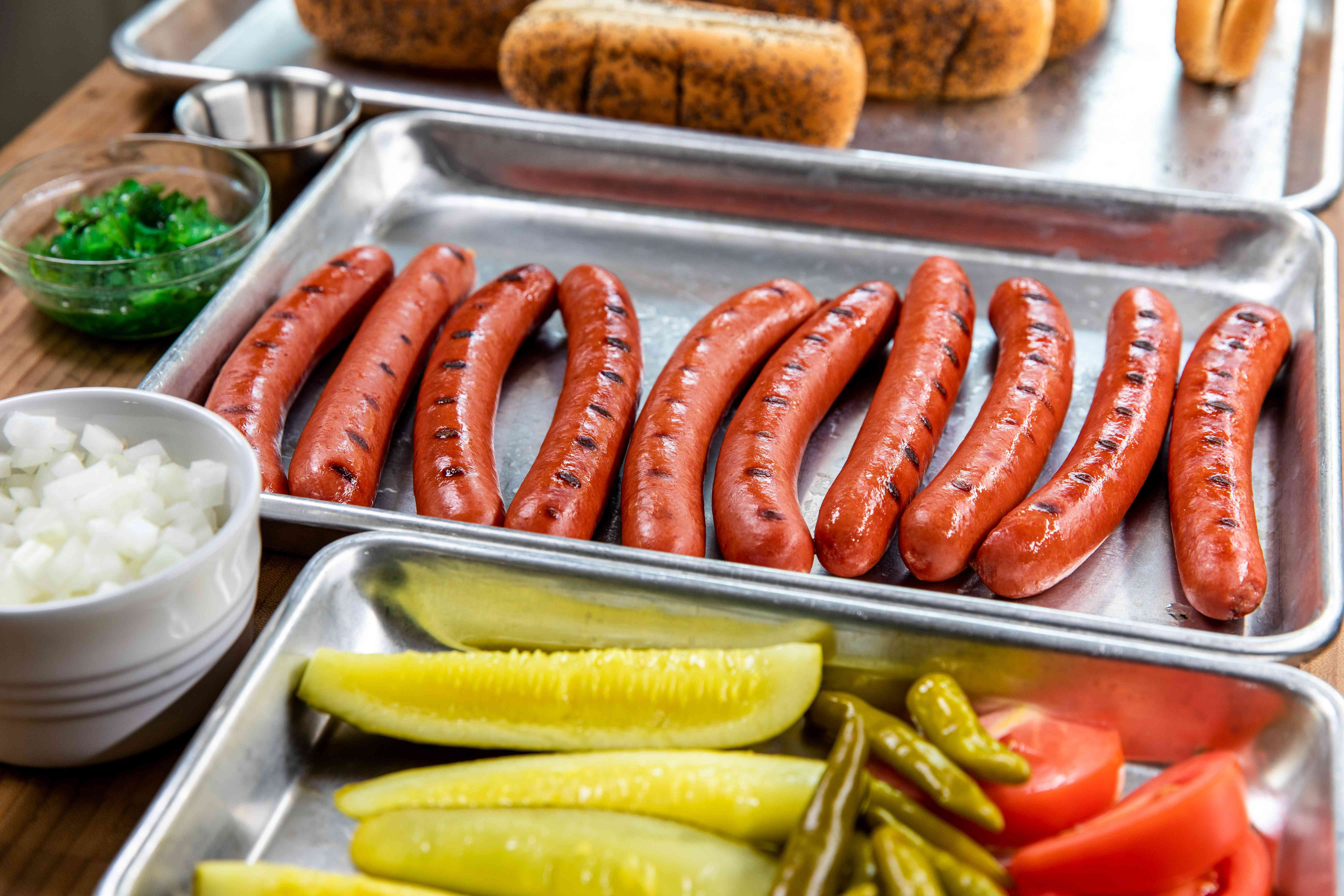 All-beef hot dog with toppings prepped on sheet pans.