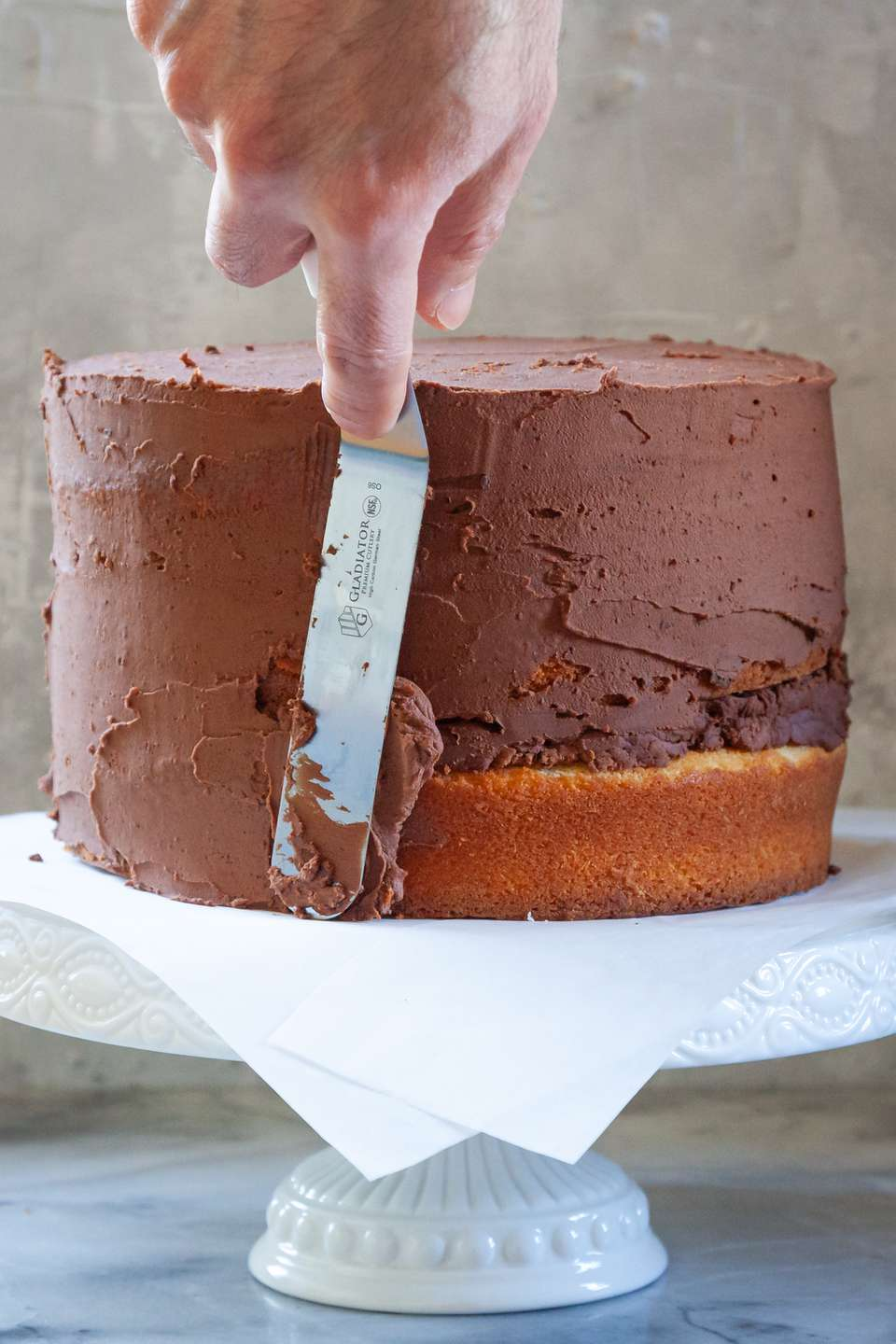 A cake being frosted with chocolate frosting on a cake stand to show cake frosting technique.