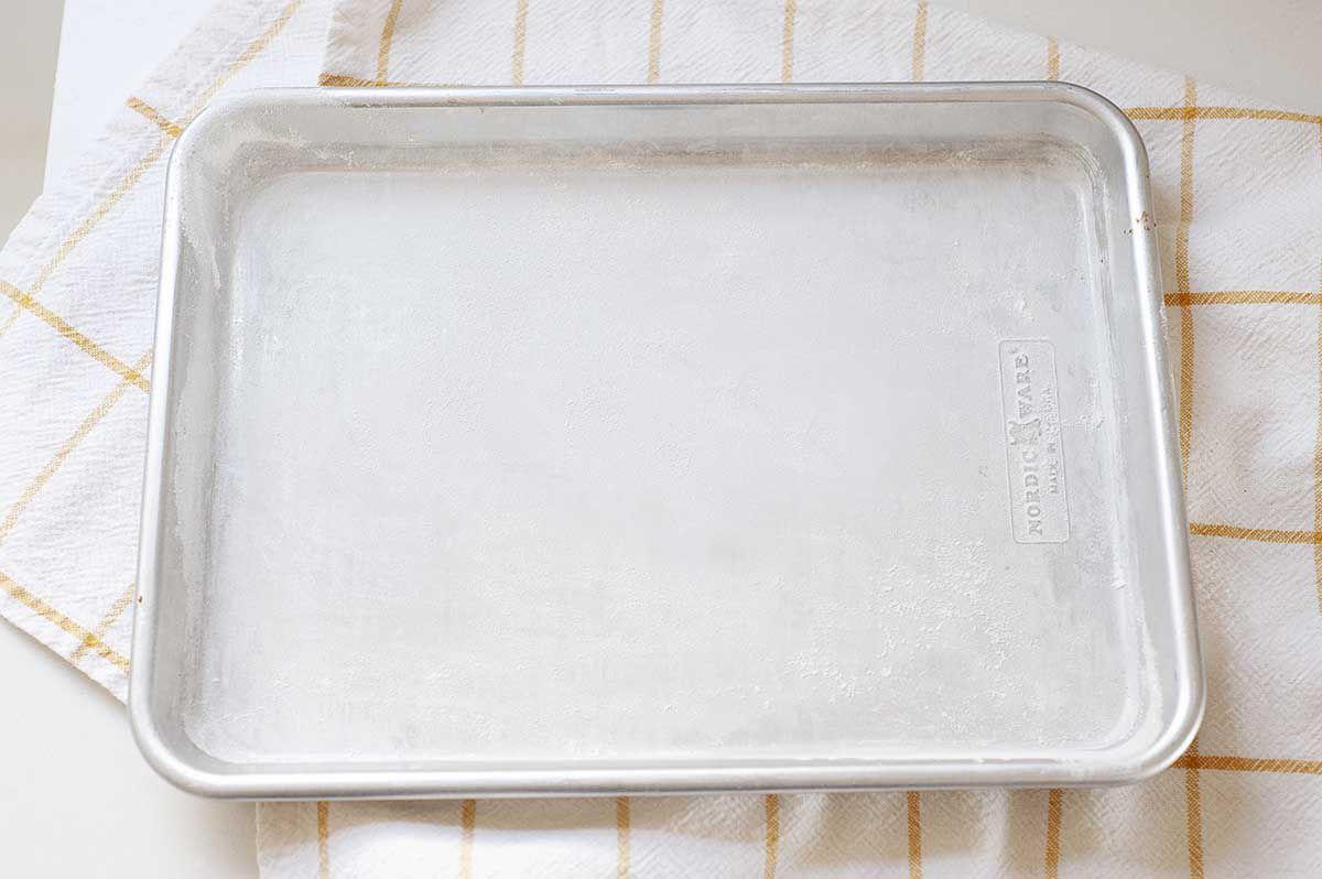 An empty baking sheet on a striped linen.