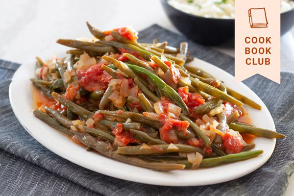 Side view of braised green beans on an oval platter.