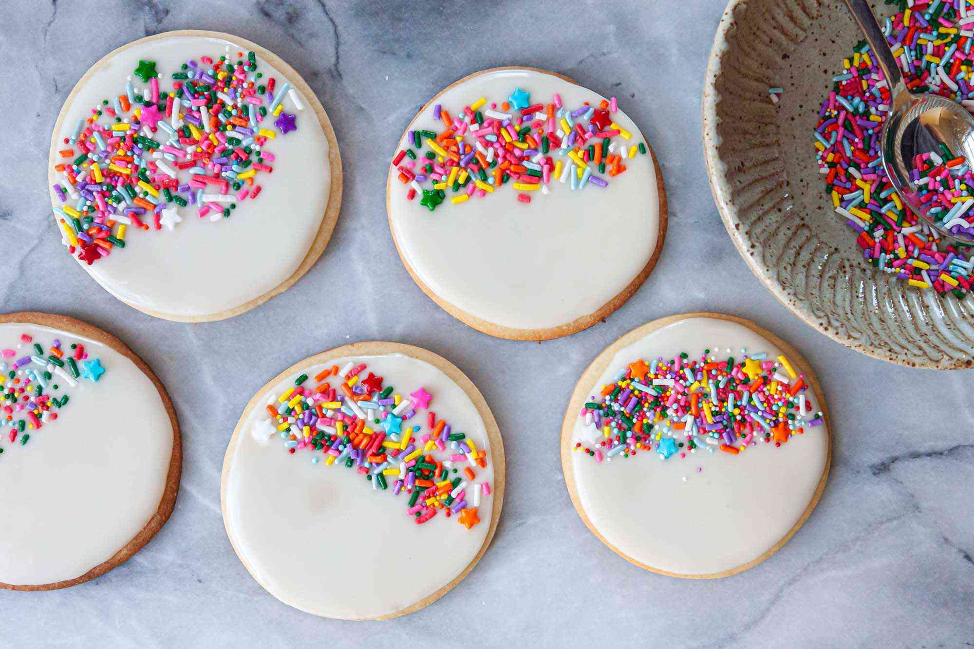 Round sugar cookies decorated with Royal icing for sugar cookies and rainbow sprinkles.