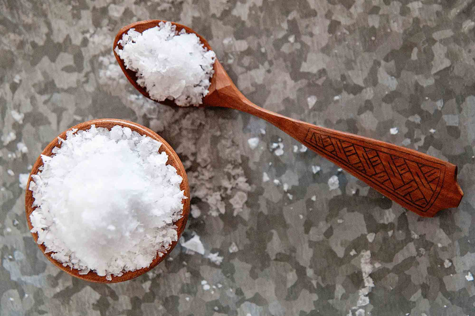 Flaky sea salt in bowl with small wooden spoon