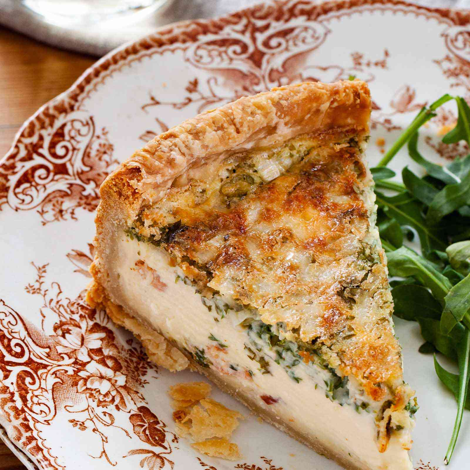 A slice of best deep dish quiche on a decorative china plate. A handful of arugula is to the right of the quiche and a table linen and glass are above the plate.
