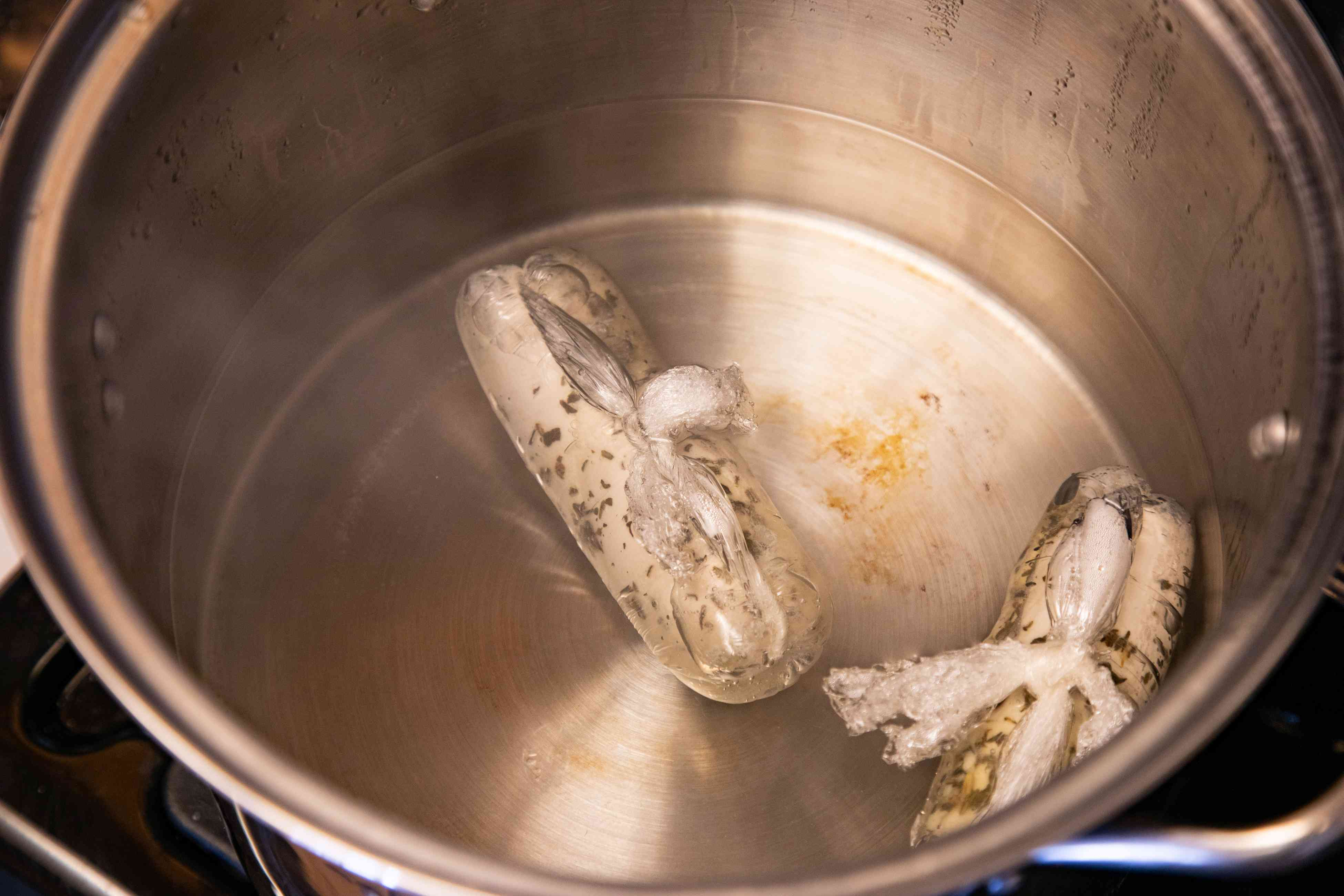 Plastic wrapped chicken in a large pot of water to make a poached chicken recipe.