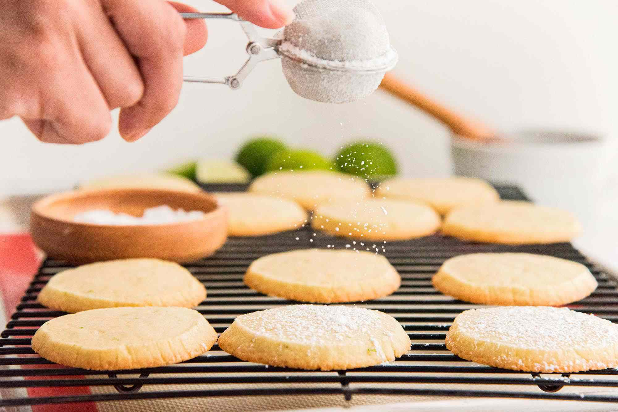Horizontal view of lime cookies on a cooling rack being coated with powdered sugar. A hand is holding a small sifter over the cookies.