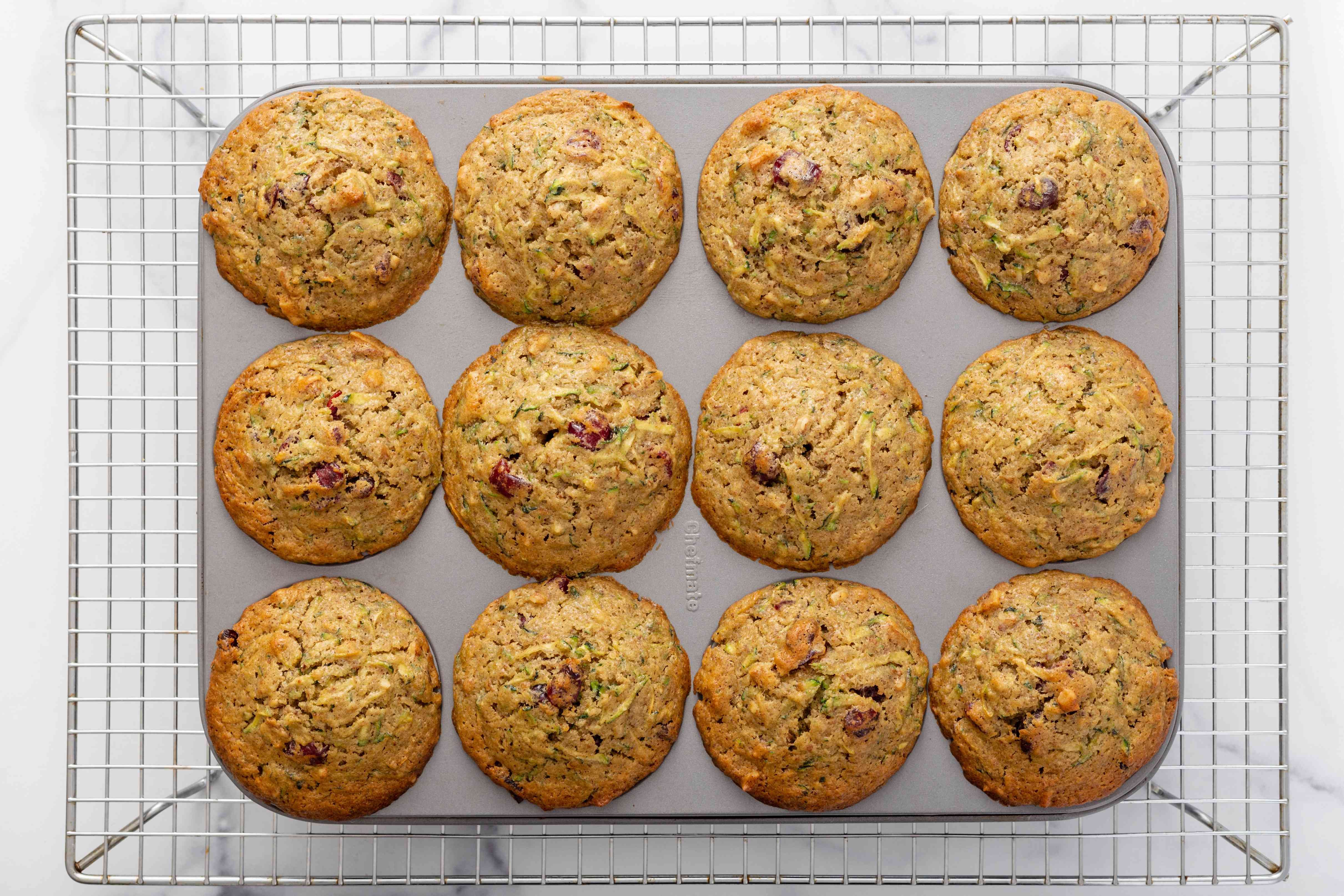 Overhead view of a muffin tin of zucchini bread muffins cooling on a rack.