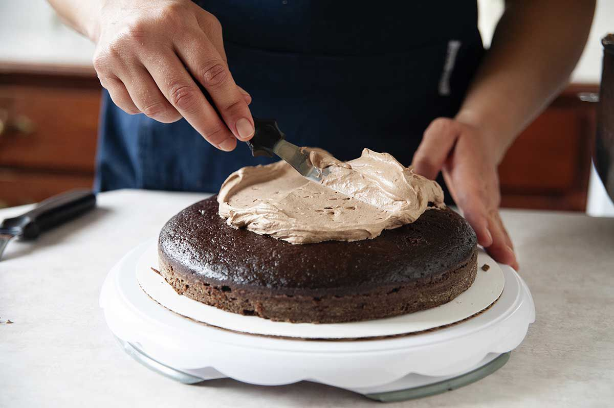 woman in blue apron frosting the bottom layer of a chocolate cake with perfect chocolate swiss meringue buttercream