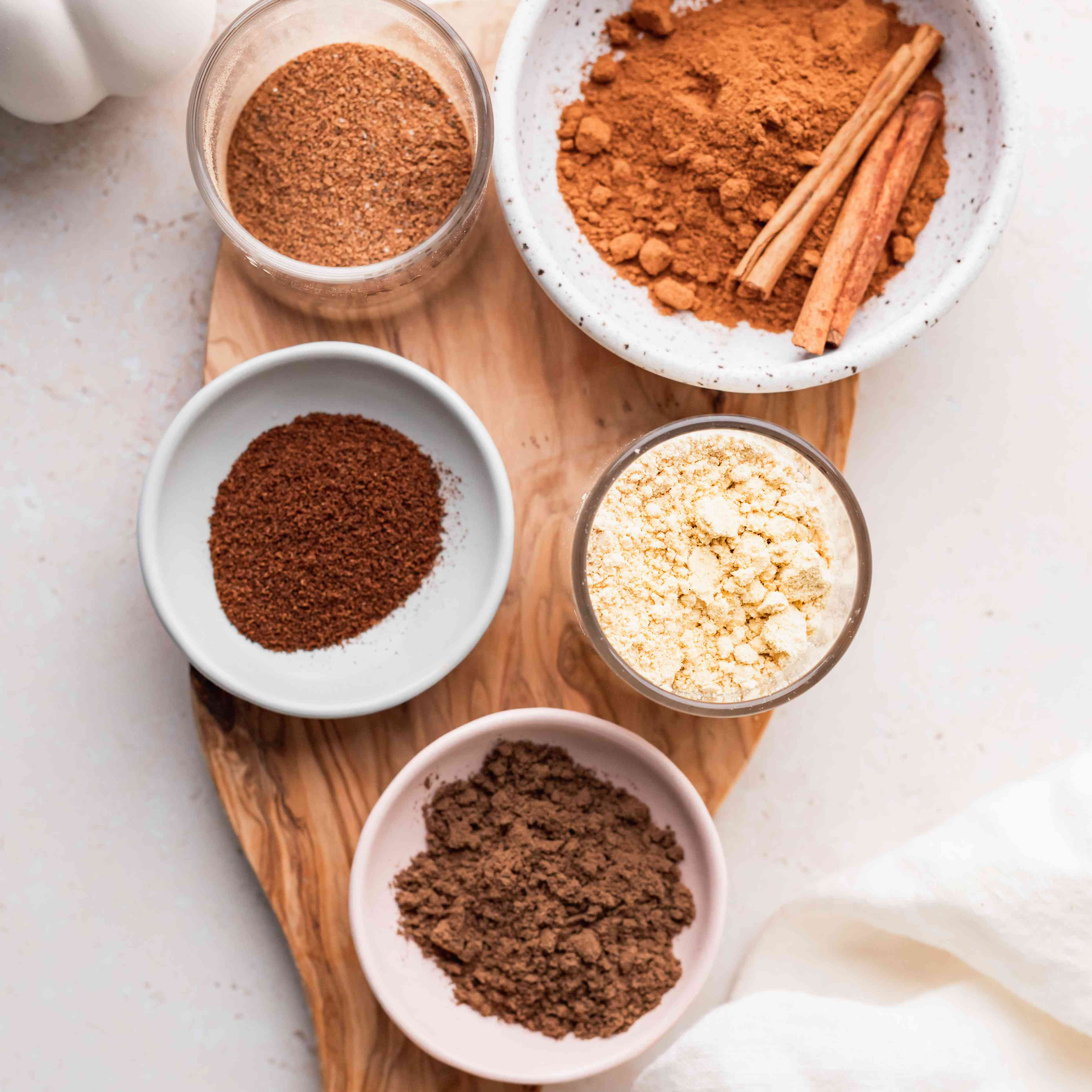 Overhead view of small bowls of individual spices set on a wooden cutting board to show how to make pumpkin pie spice.