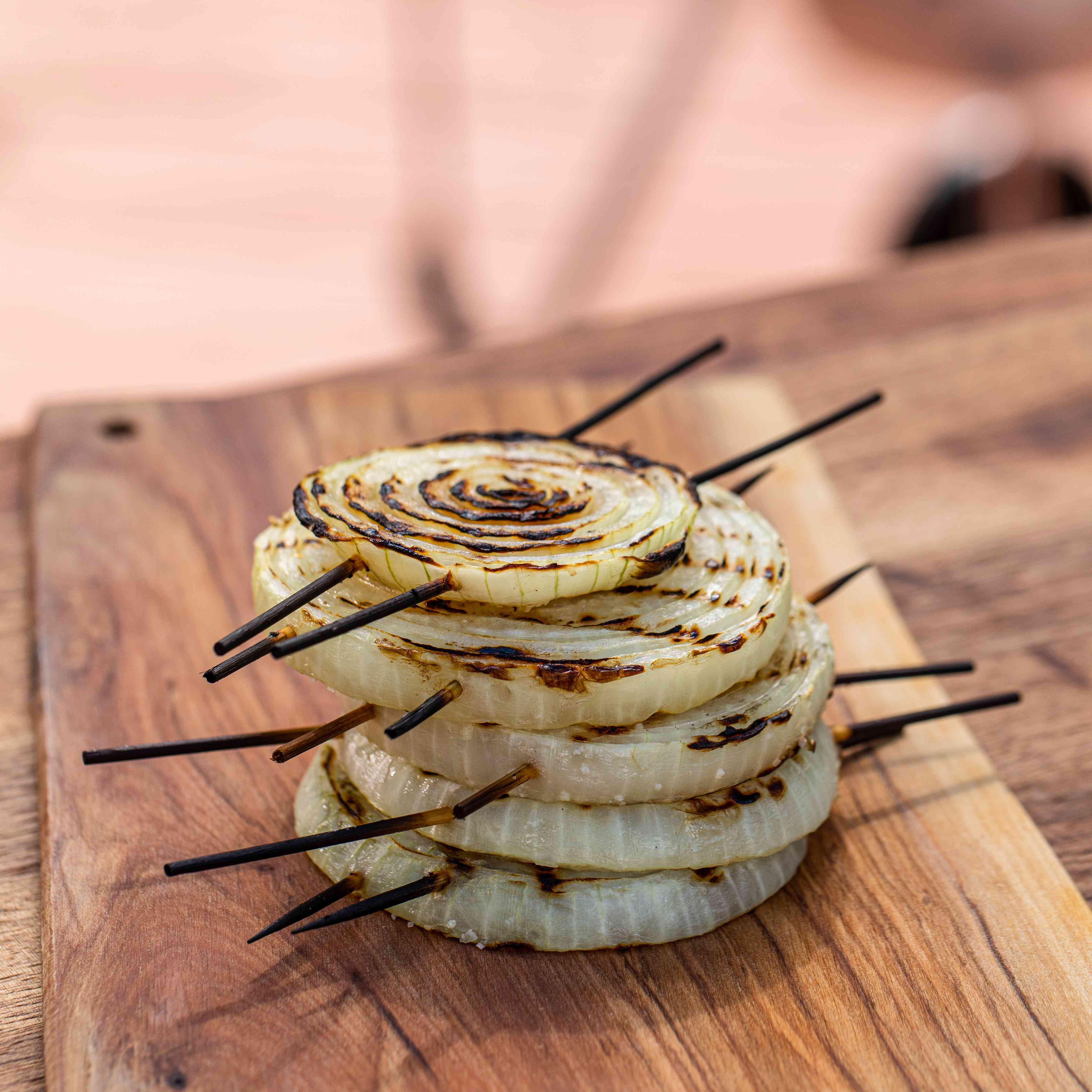 Easy grilled onions on skewers set on a wooden board.