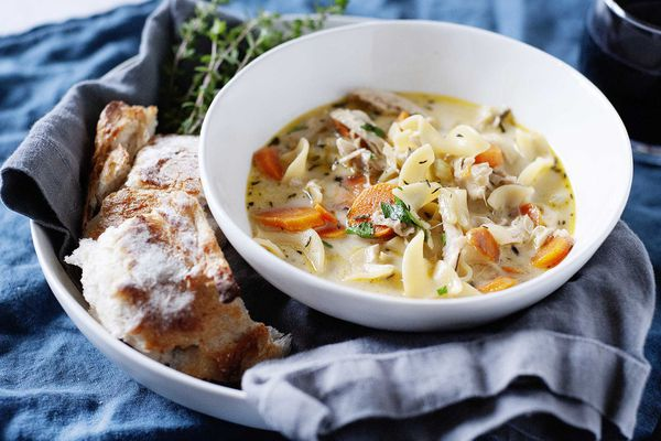 A white bowl filled with the best creamy chicken noodle soup set on a grey linen against a blue background with a bundle of thyme near by and a hunk of sourdough bread..