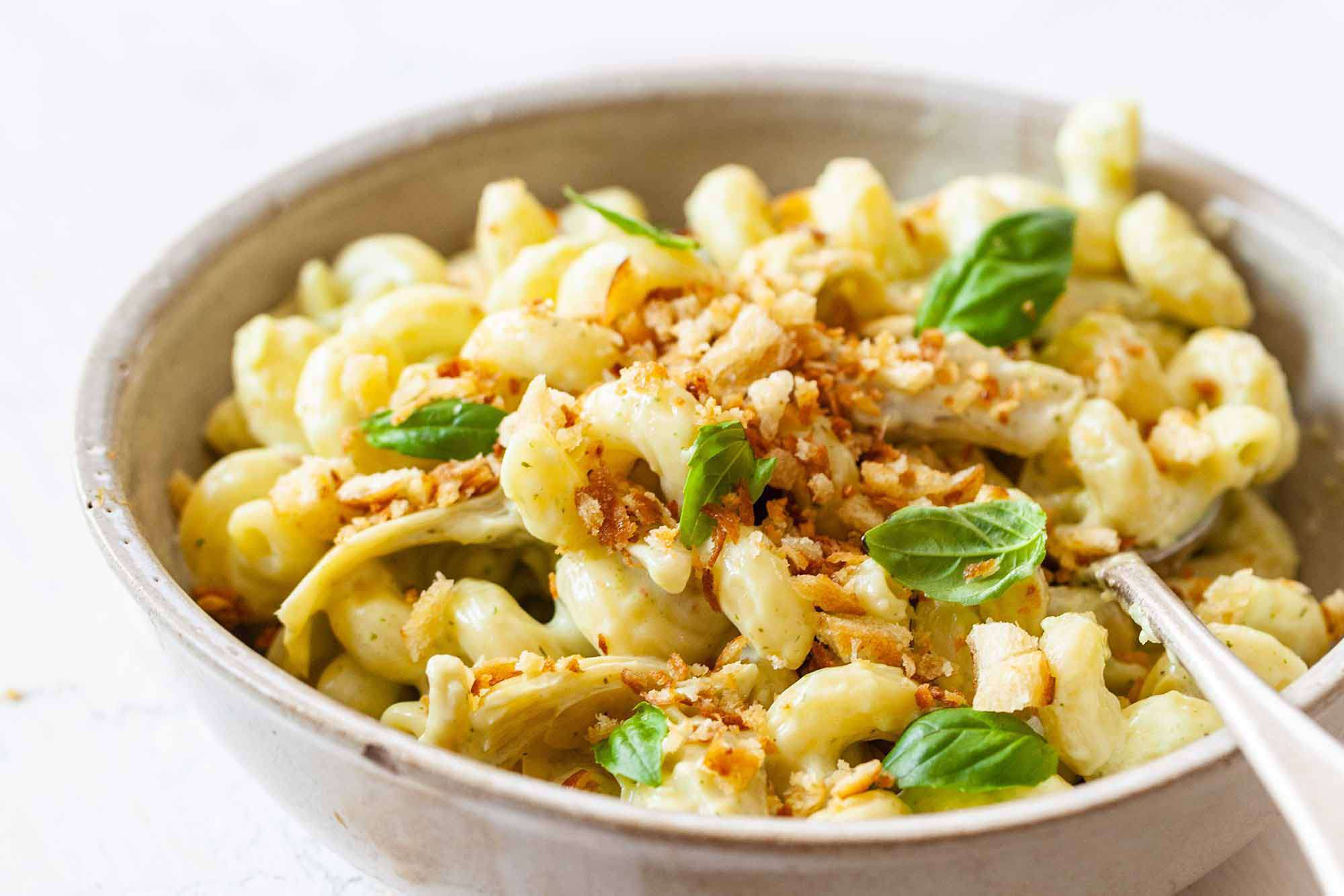 Mac and Cheese Add-Ins - mac and cheese in bowl with basil leaves and breadcrumbs on top
