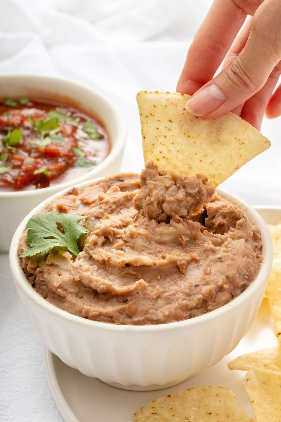 Dipping tortilla chip into a bowl of homemade refried beans.