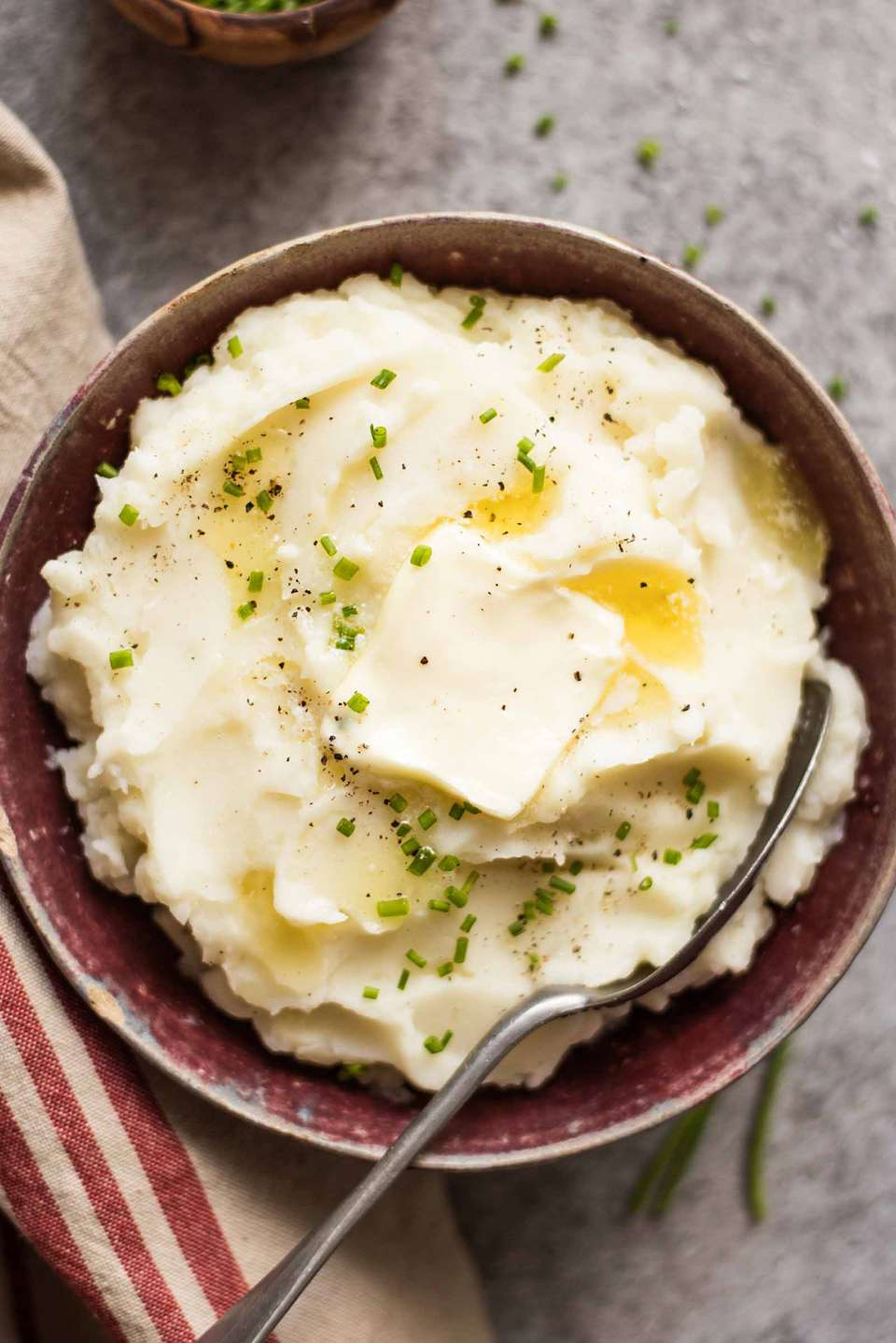 Crockpot Mashed Potatoes Recipe potatoes in a bowl with butter and chives and a spoon in it