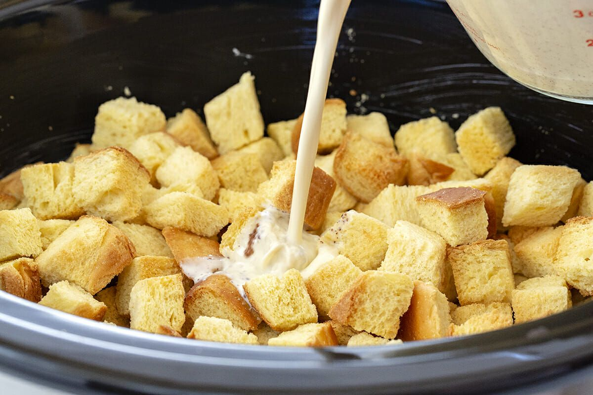 Make Ahead French Toast Casserole - milk being poured over bread cubes in slow cooker