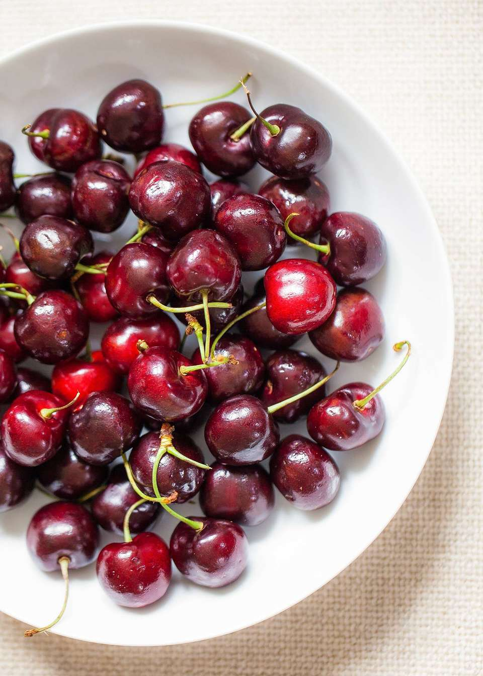 A white bowl filled with red cherries.