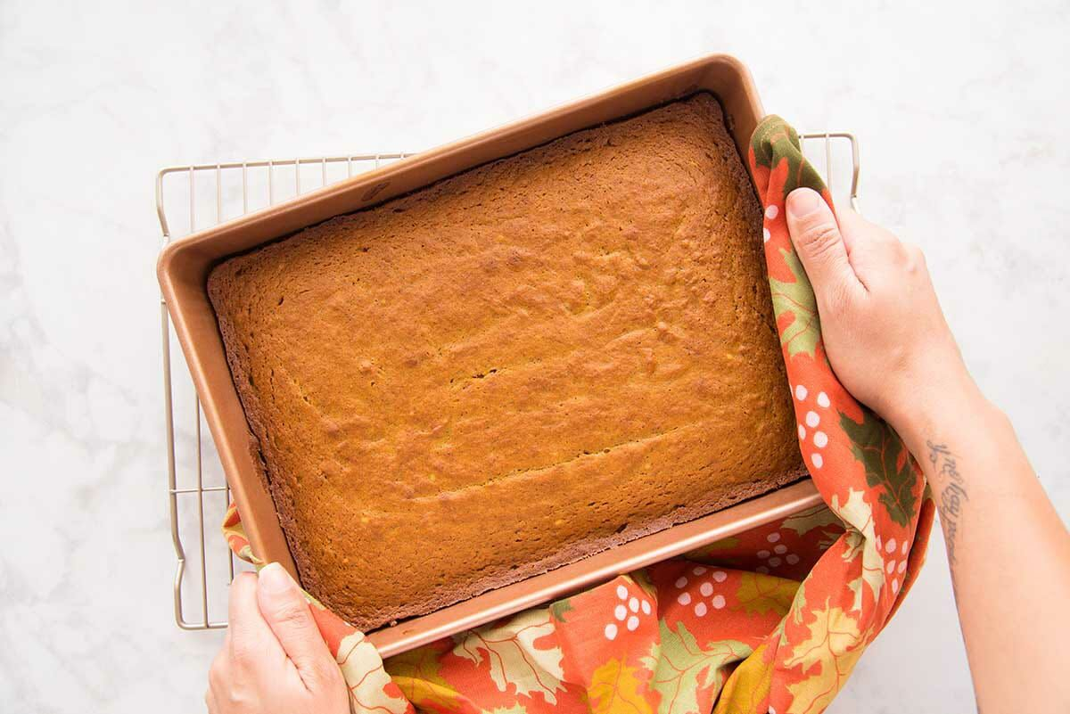 Pumpkin Snack Cake in a pan and held above a cooling rack.