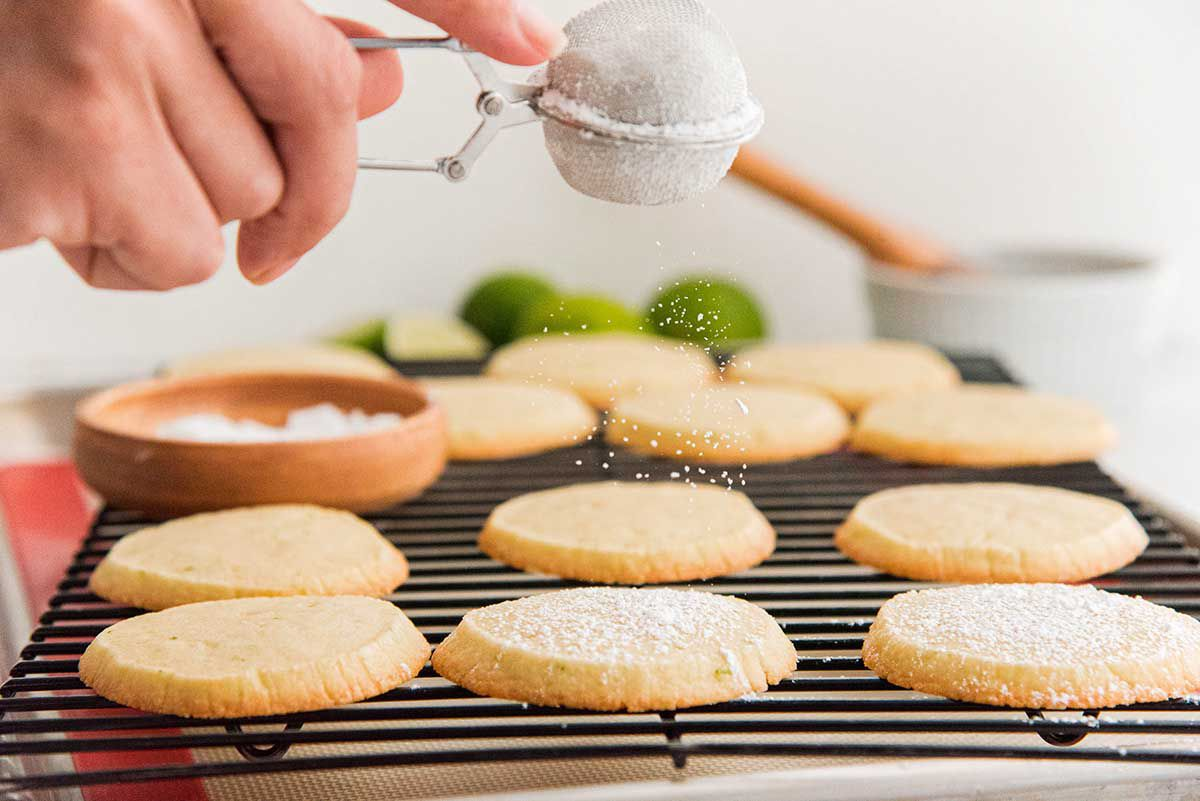 Lime cookies are being coated with powdered sugar using a small sifter.