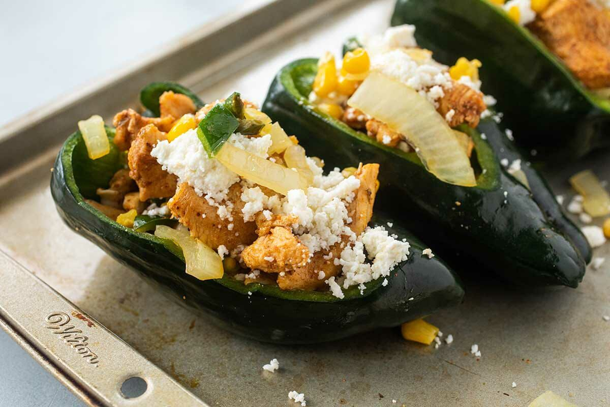 Three of The Best Stuffed Peppers on a baking sheet topped with crumbled cheese, sauteed onions and sliced chicken.
