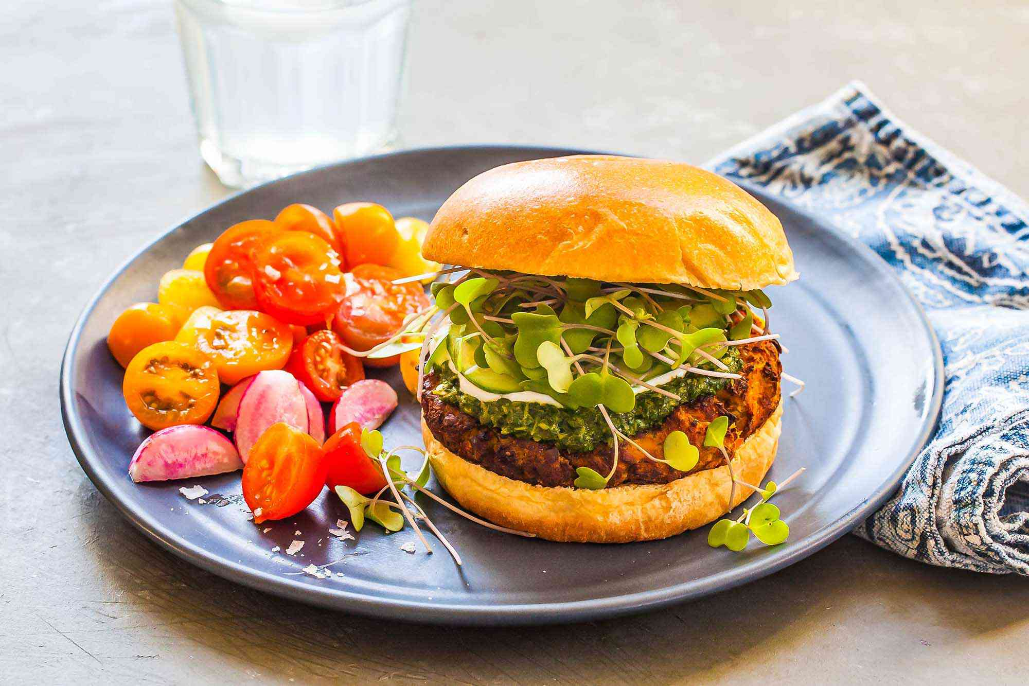 A blue plate has an indian spiced lentil burger set next to halved grape tomatoes. The lentil patty, chutney and sprouts are visible inside the bun. A blue patterned napkin is folded next to the plate.