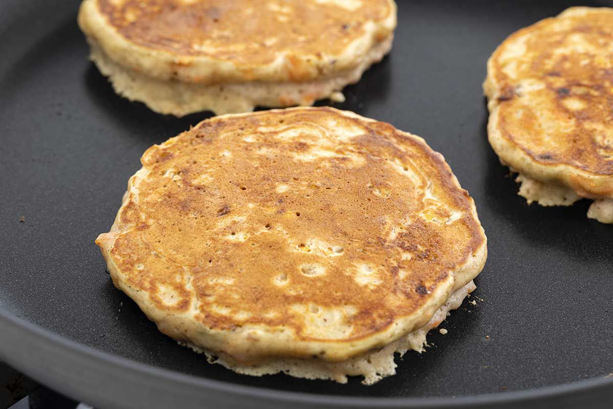 Buttermilk carrot cake pancakes are cooking on a griddle. The top is golden.