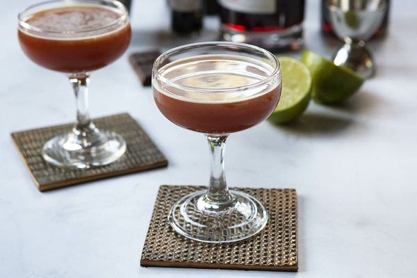 Sidecar drink with chocolate in a coupe glass with a second glass behind it. Ingredients for the cocktails are behind the glass.