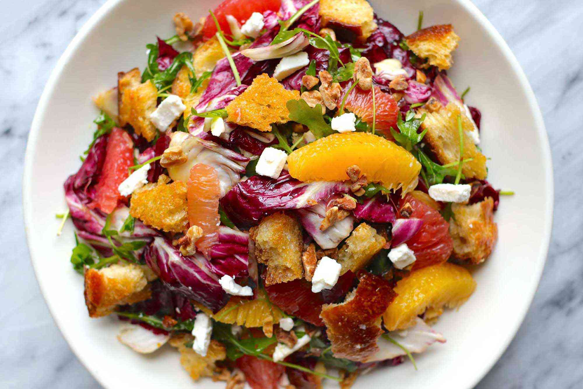 Horizontal overhead view of citrus salad on a white plate. Supremed orange and grapefruit, radicchio, croutons and feta cheese crumbles are visible.