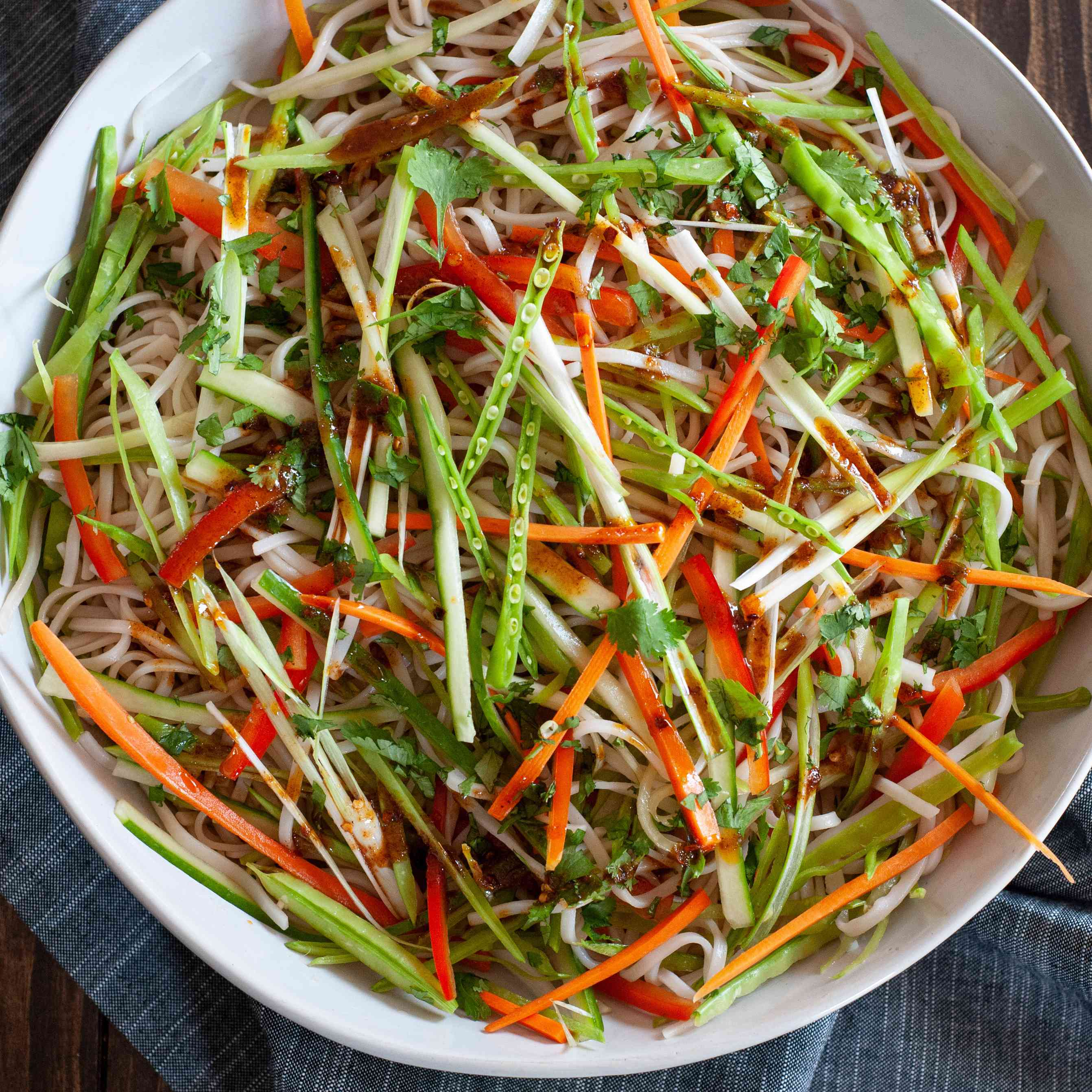 Vegetable rice noodle salad in a serving bowl with a linen underneath.