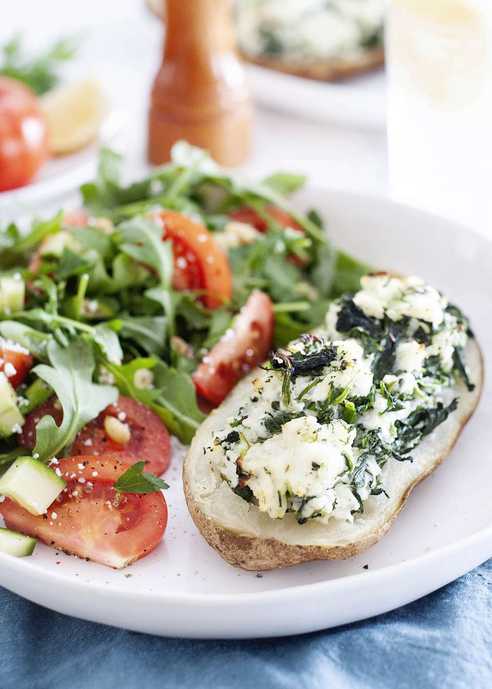 Twice baked potato filled with spinach and feta on a white plate with a tomato and arugula salad.