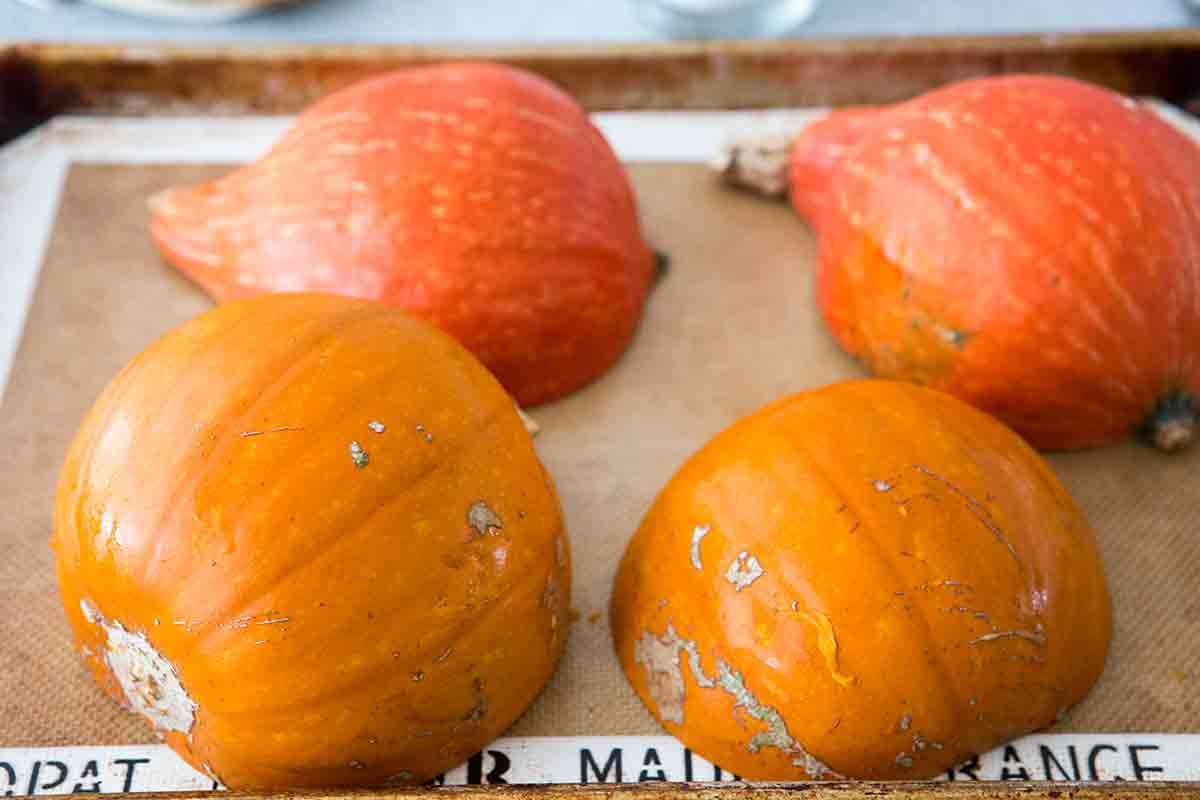 cut sugar pumpkins kabocha squash in half, scoop out seeds, place cut side down on lined baking sheet