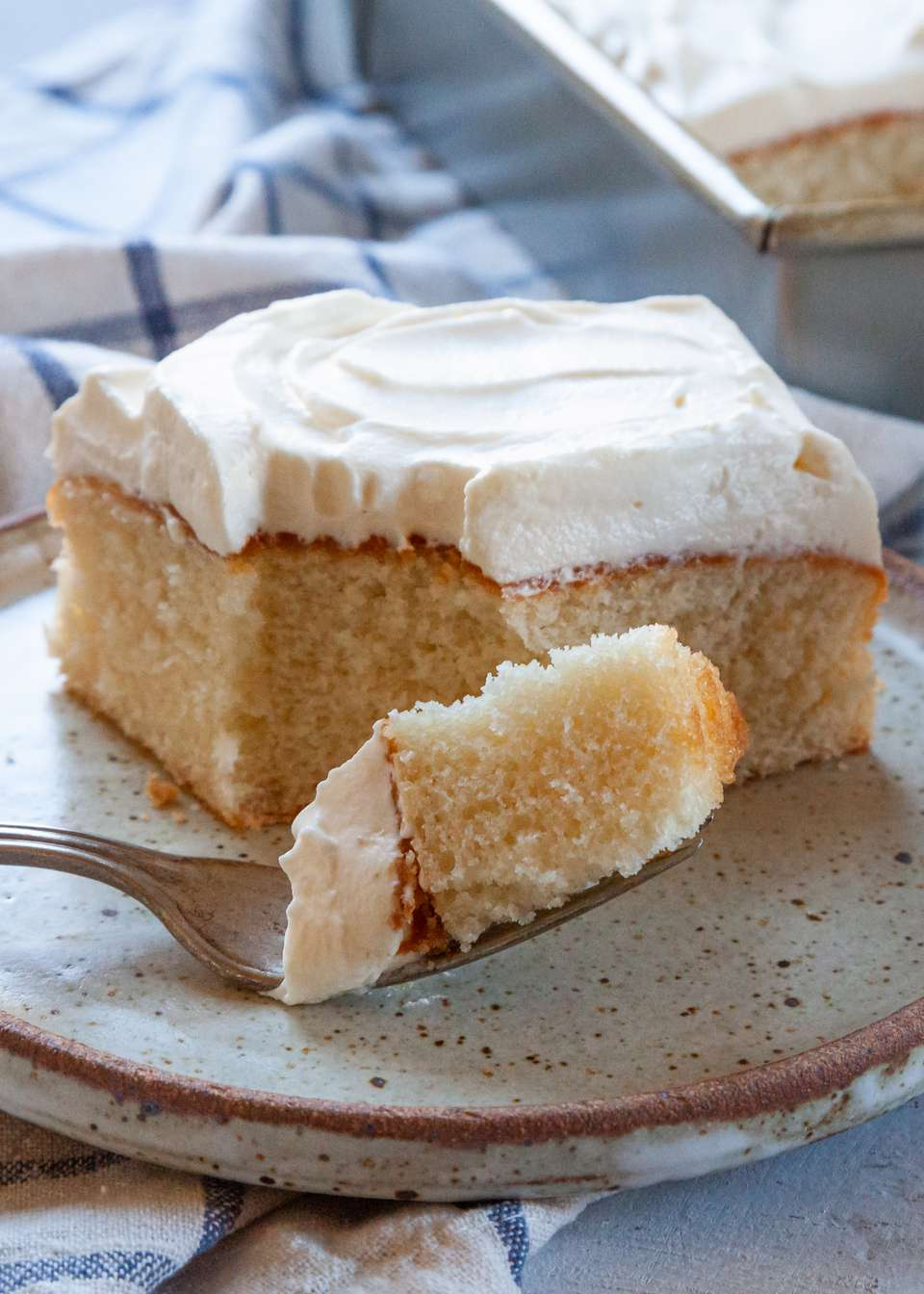 Side view of a copycat box white cake topped with frosting and on a plate with a bite on a fork.