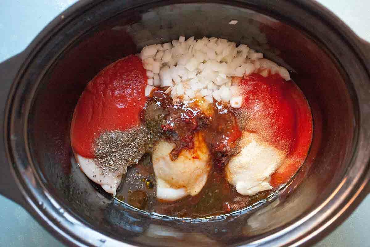 Ingredients for slow cooker chicken tacos in the crockpot: chicken breasts, spices, onions, honey, tomato sauce, and chipotle