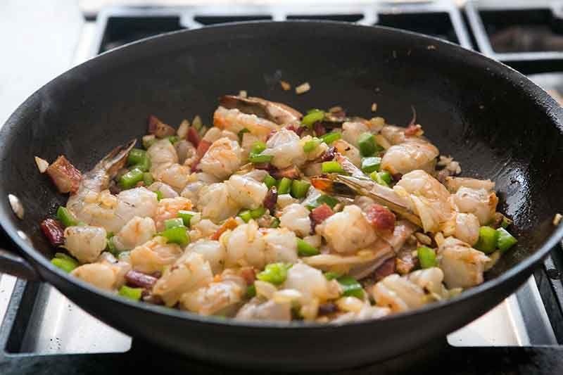 adding shrimp to sauteed vegetables