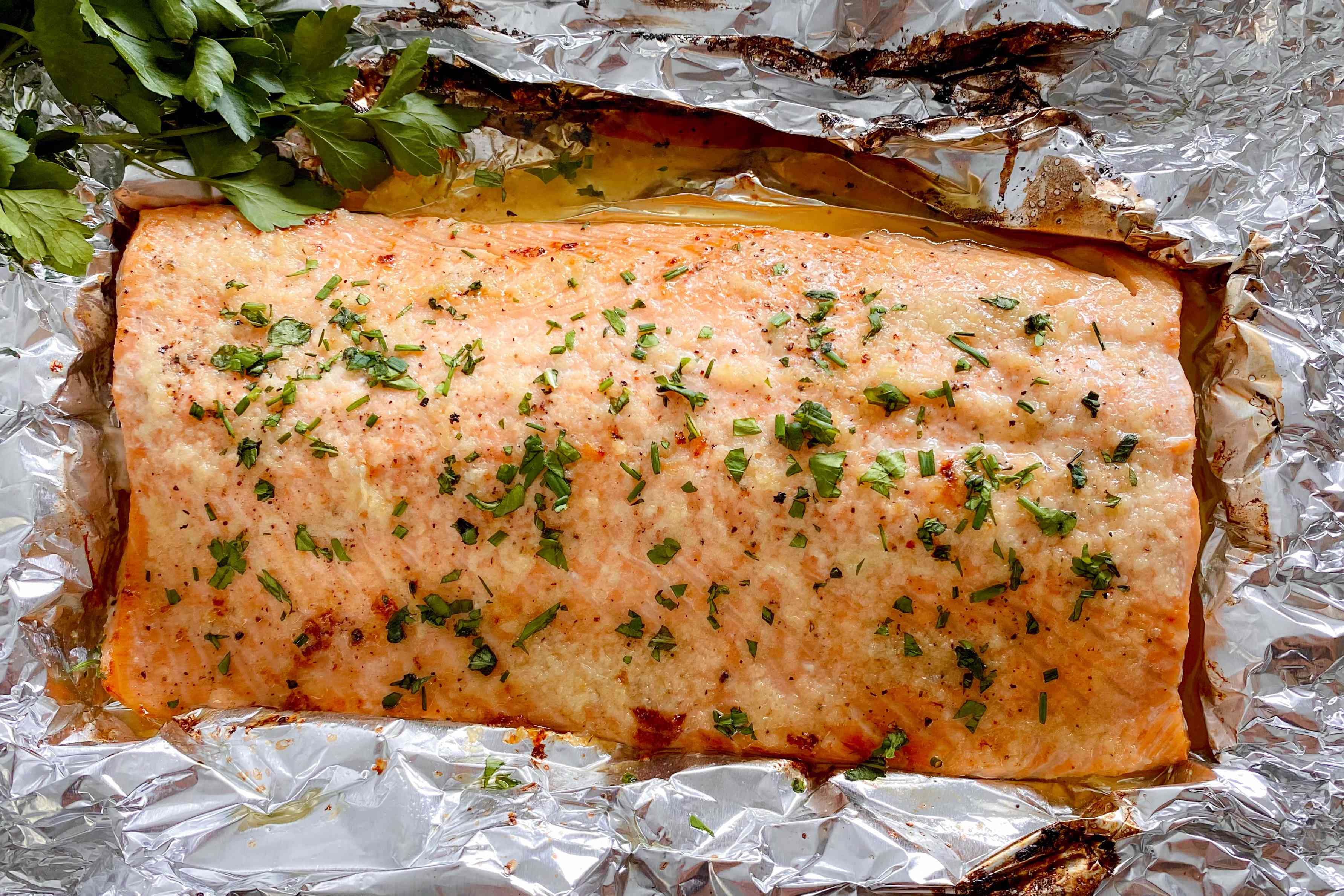 Honey Garlic Butter Roasted Salmon topped with herbs and set on foil.