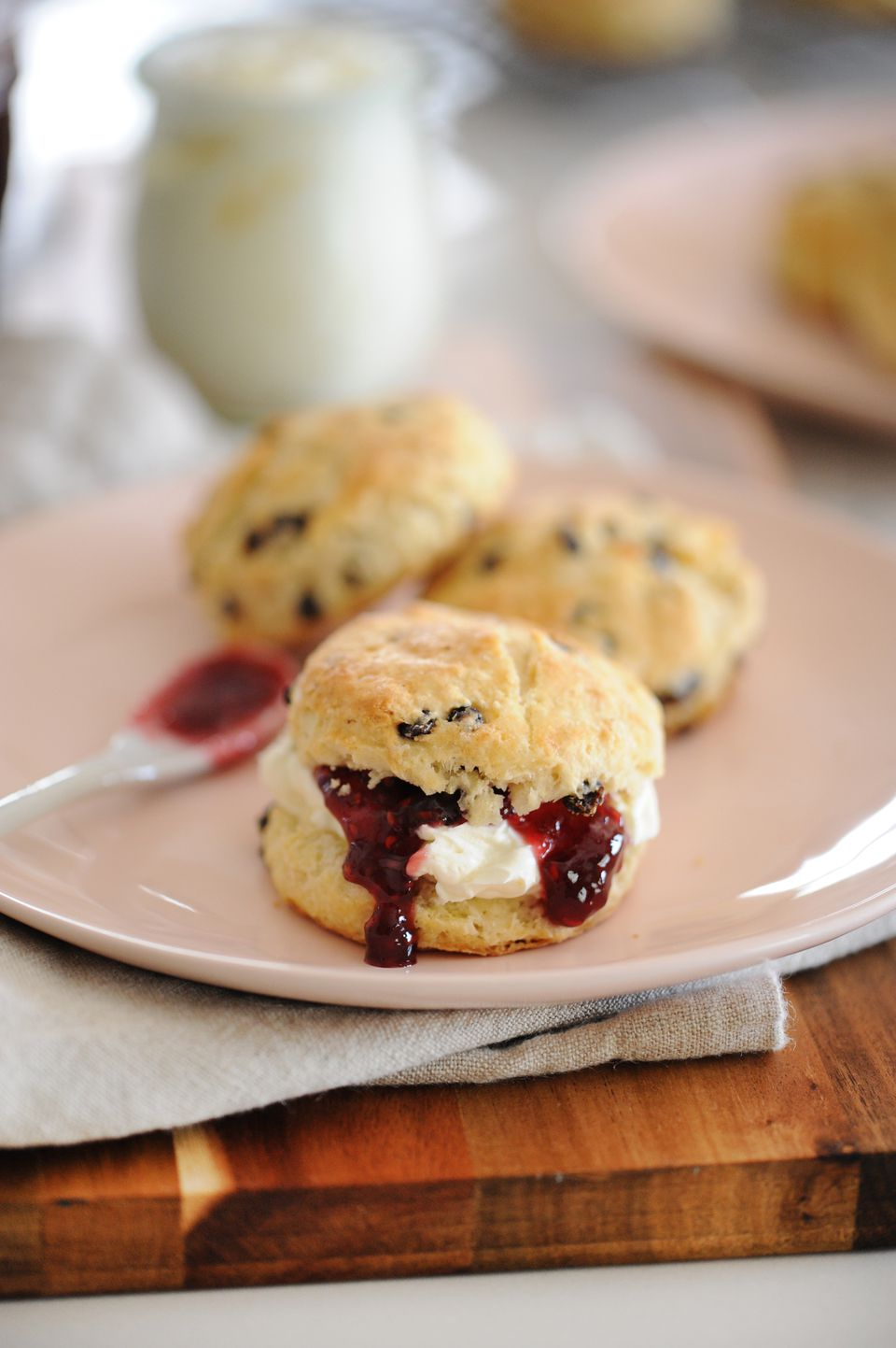 Real Irish Scones spread with jam and set on a plate.