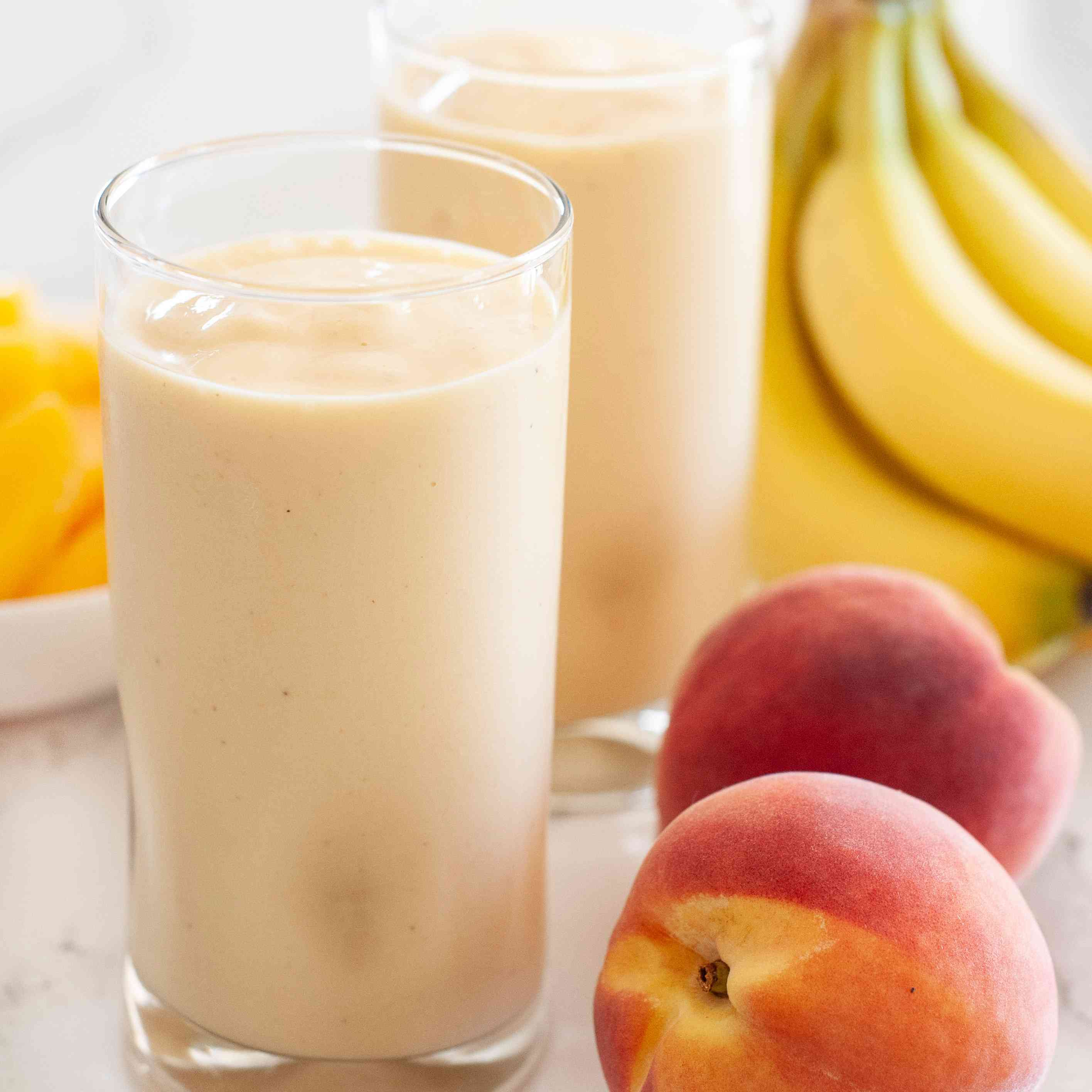 Peach smoothie with almond butter in glasses with fresh peaches and bananas to the right.