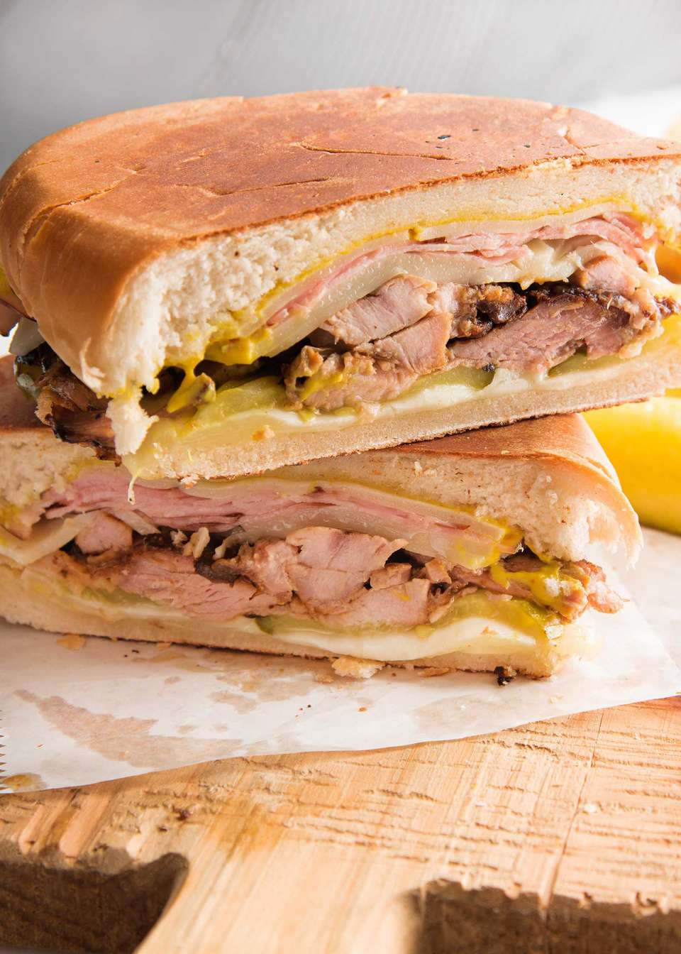 Two halves of a grilled cuban sandwich are resting on parchment paper and a wooden cutting board. The shredded pork, cheese, mustard and mayonnaise are visible.