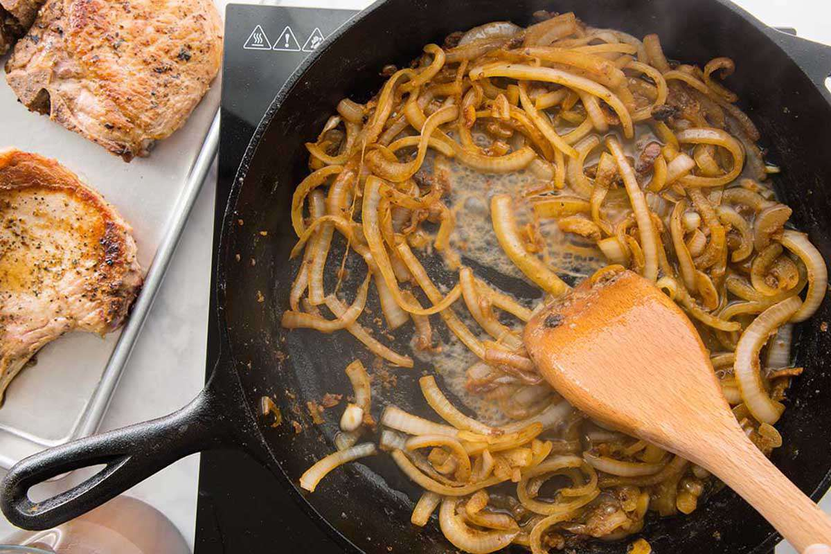 Onions sauteed in a cast iron skillet with a wooden spoon.