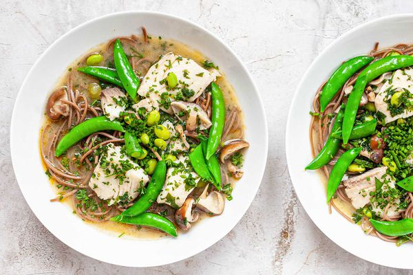 Two white bowls filled with quick and easy Miso Soup with fish, peas, herbs and soba noodles on a marble background.