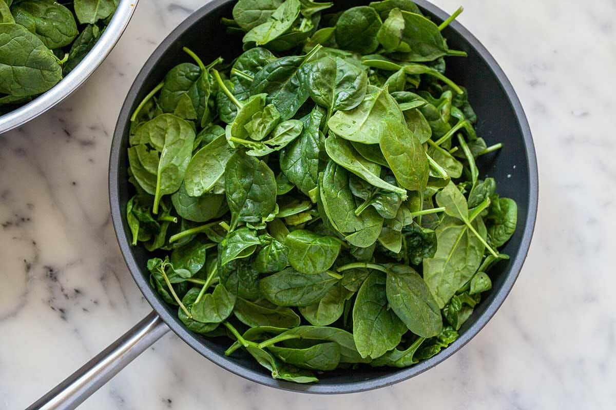 A non-stick skillet filled with fresh spinach to make Spinach in Creamed Mustard Sauce.