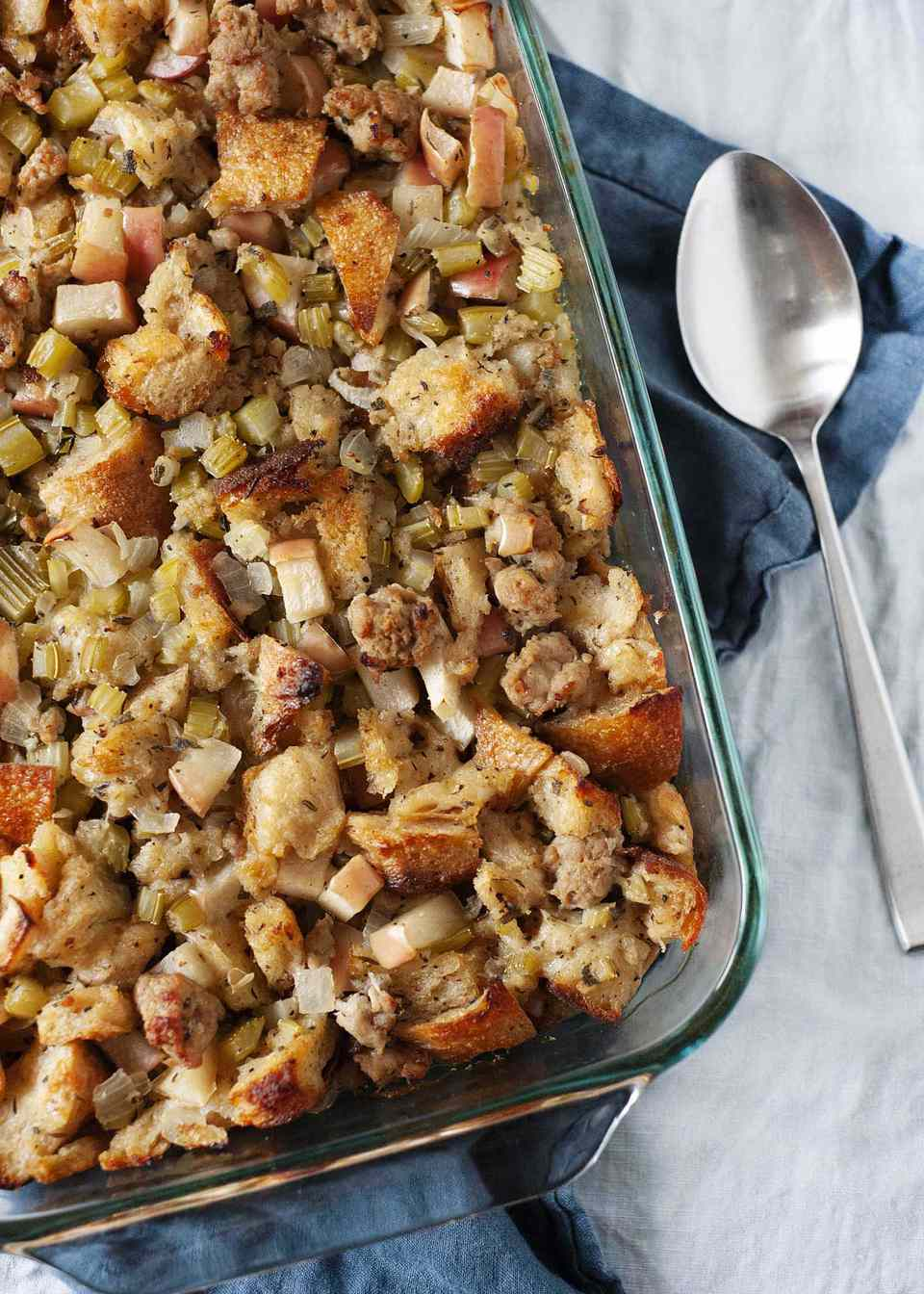 Thankgiving stuffing in a baking dish on a blue napkin with a silver spoon nearby.