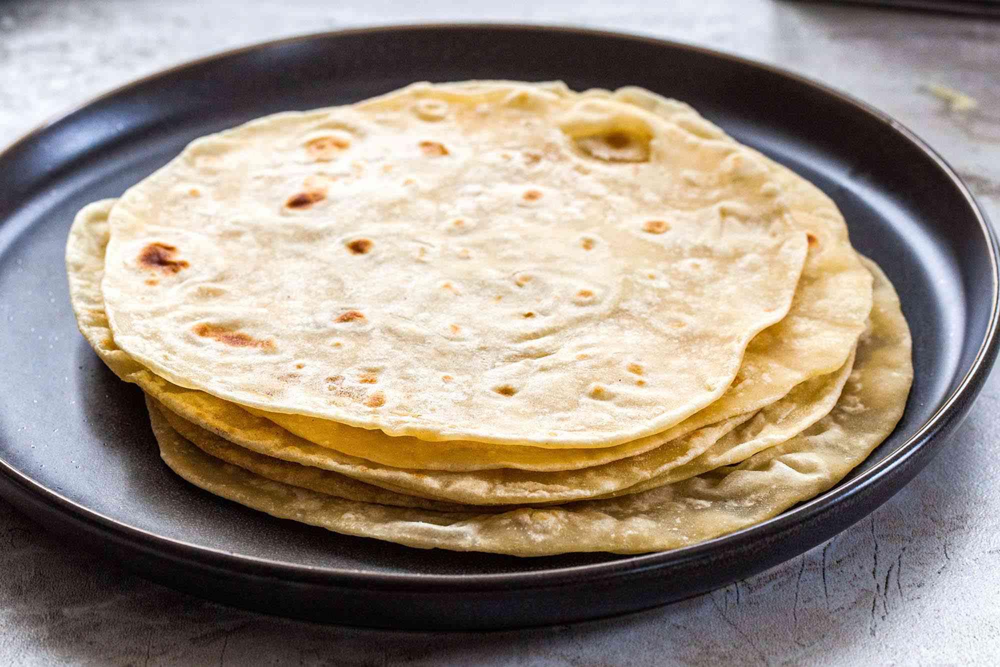 Homemade flour tortillas on a platter.