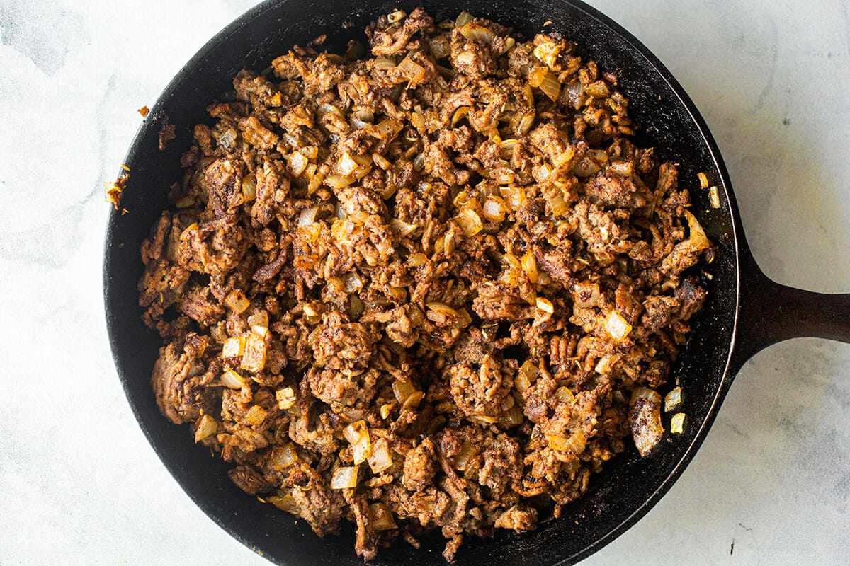 Ground beef in a cast iron skillet for Easy Slow Cooker Beef and Bean Chili.